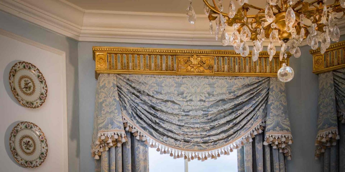 Immerse yourself in a light-filled room with classical drapes and impeccable sparkling crystal chandeliers