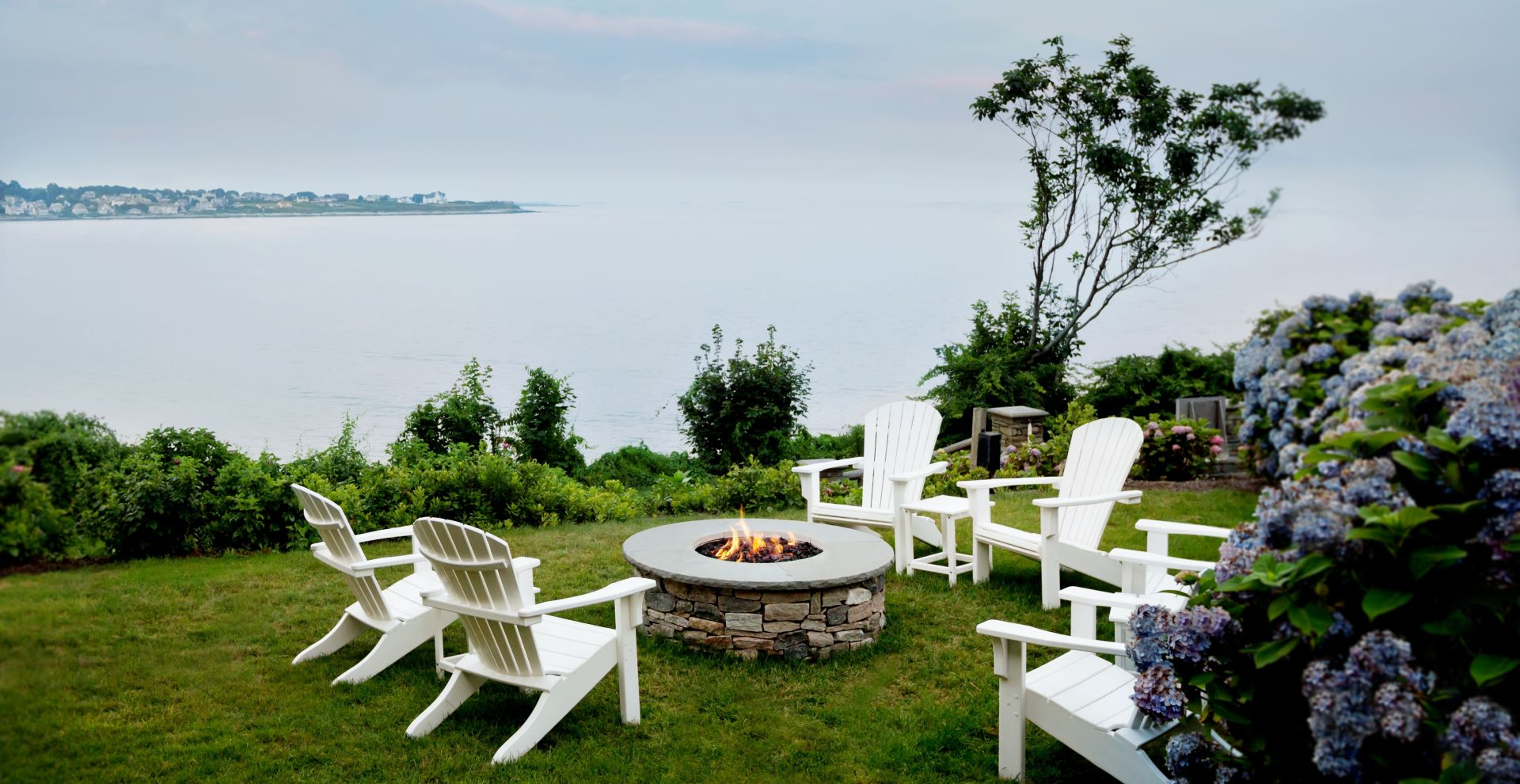backyard view of ocean with a fire pit at The Chanler at Cliff Walk